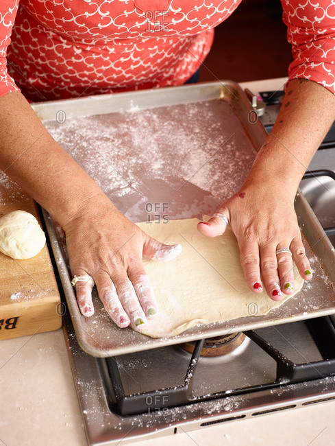 Woman placing large flattened dough onto a pan