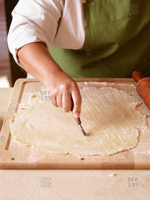 Baker cutting lattice strips out of dough for pie topping