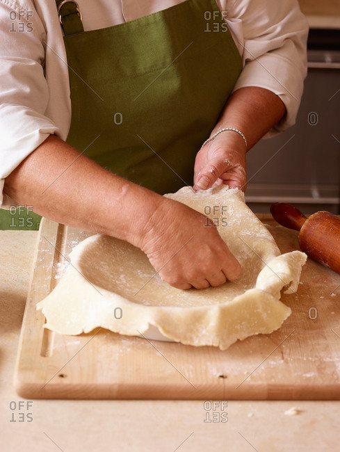 Baker putting pie crust into pie dish