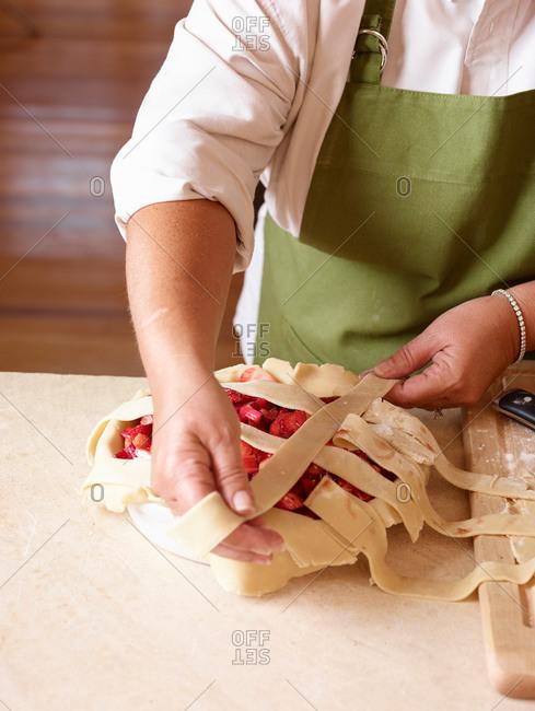 Baker arranging lattice on strawberry-rhubarb pie