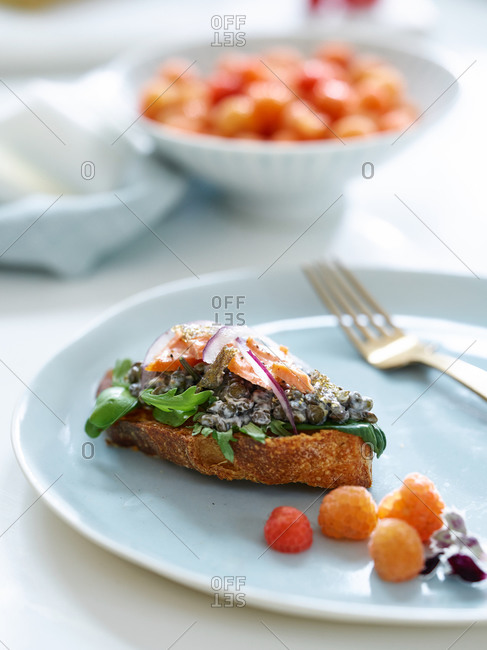 Plate with salmon appetizer and white raspberries
