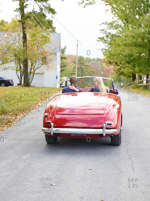 Couple riding in old red convertible