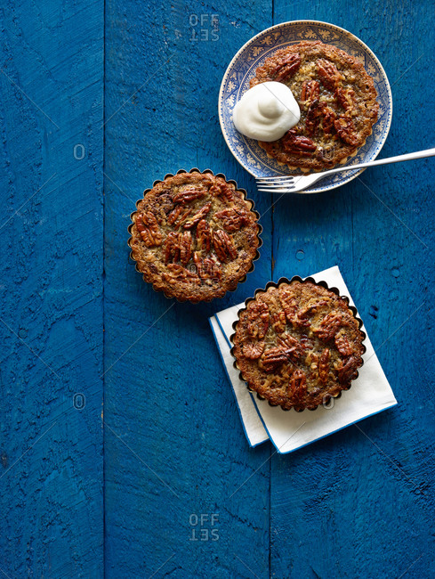 Three mini pecan pies with whipped cream on one