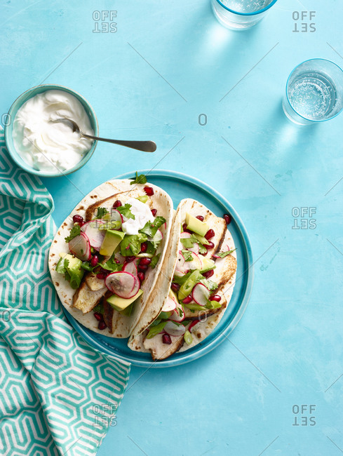 Spiced chicken tacos with avocado and pomegranate salsa with sour cream
