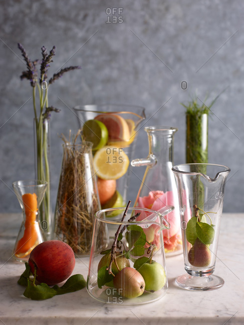 Various glassware filled with fruit and leaves