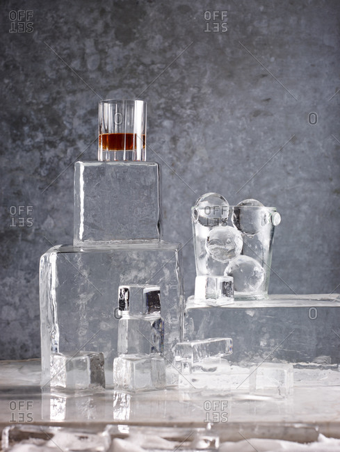 Shaped ice arranged on a table and topped with a glass of whiskey