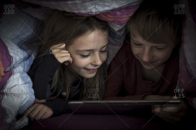 Brother and sister lying side by side using digital tablet under a blanket
