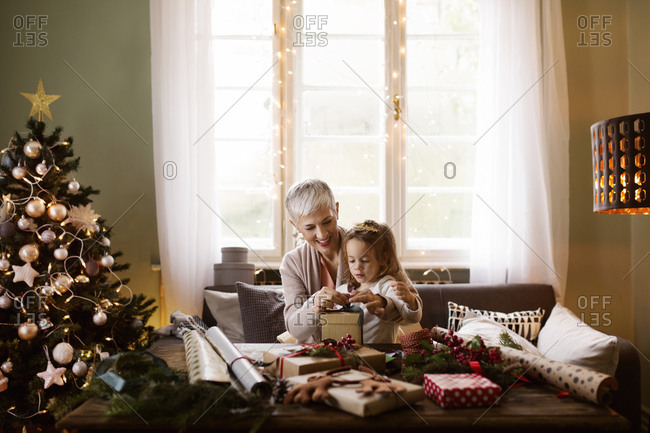 Grandmother and child wrapping Christmas presents