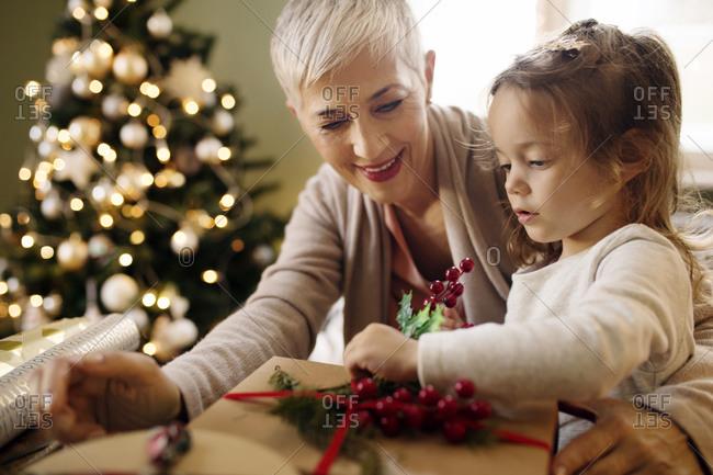 Grandmother helping child wrap Christmas presets