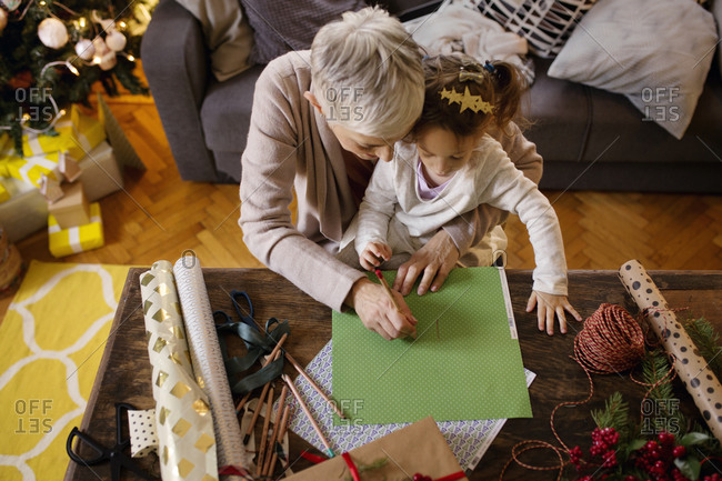 Woman helping her granddaughter with Christmas wrapping