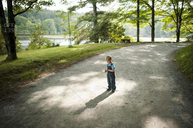 Boy looking at leaf at a park