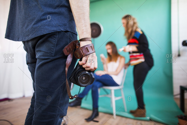 Photographer waiting for makeup artist and model during photo shoot