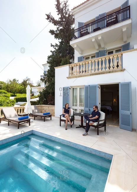 Paphos, Cyprus - May 8, 2015: People sitting poolside, Paphos, Cyprus