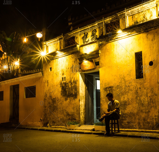 Hoi An, Vietnam - April 23, 2015: A man sits on a stool outside a restaurant while looking at his cellphone at night time in the town of Hoi An, Vietnam