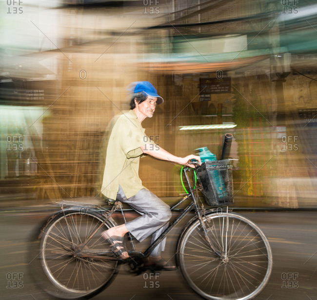 Hanoi, Vietnam - May 15, 2015: A local Vietnamese man in a blue cap riding his bicycle through the streets of Hanoi, Vietnam