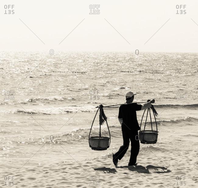 A beach vendor carrying his produce using a shoulder pole or 'Yoke' along a beach in Phu Quoc Island, Vietnam
