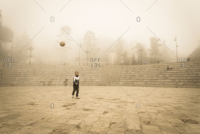 Sapa, Vietnam - May 11, 2011: A young Vietnamese boy kicking a soccer ball around on his own in an amphitheater on a misty morning in the center of Sapa, Vietnam