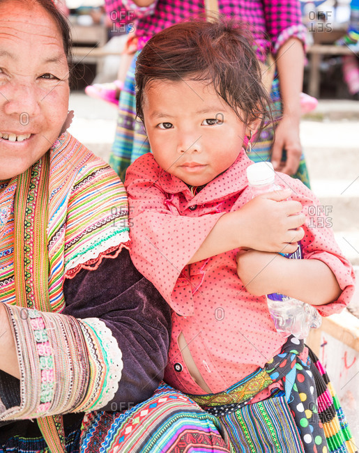 Bac Ha, Lao Cai Province, Vietnam - May 9, 2015: Young Vietnamese girl standing with her Grandmother in Bac Ha, Lao Cai Province, Vietnam