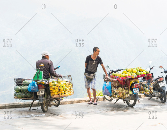 Sapa, Vietnam - May 10, 2011: Two male fruit vendors with their motorbikes loaded up with freshly picked mangos and melons in the town of Sapa, Vietnam