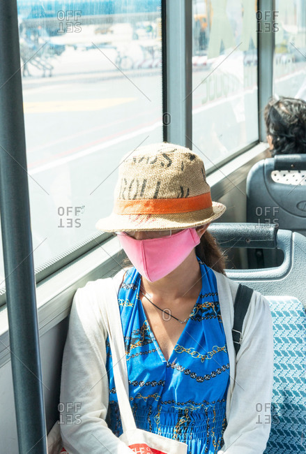 Young woman in a pink, face mask and summer, hat riding, on an airport shuttle bus in Saigon, Vietnam