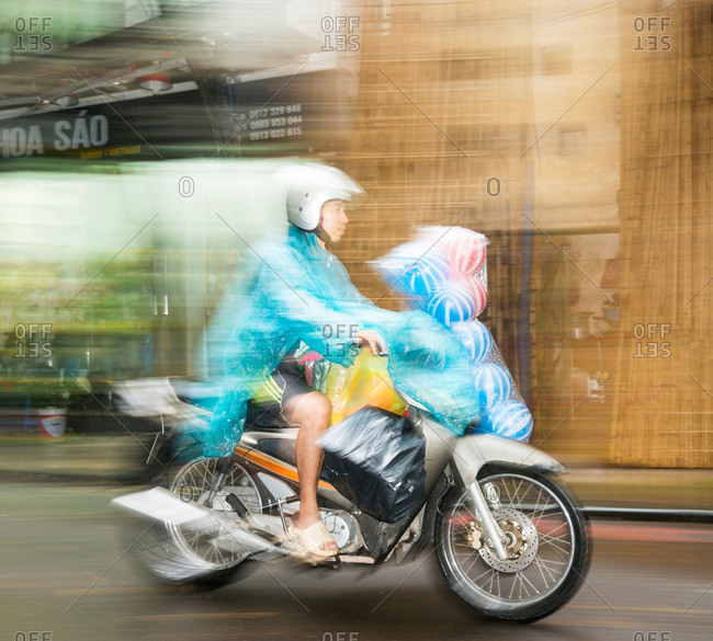 Hanoi, Vietnam - May 15, 2015: A man transporting striped soccerballs on the front of his motorbike in the rain, Hanoi, Vietnam