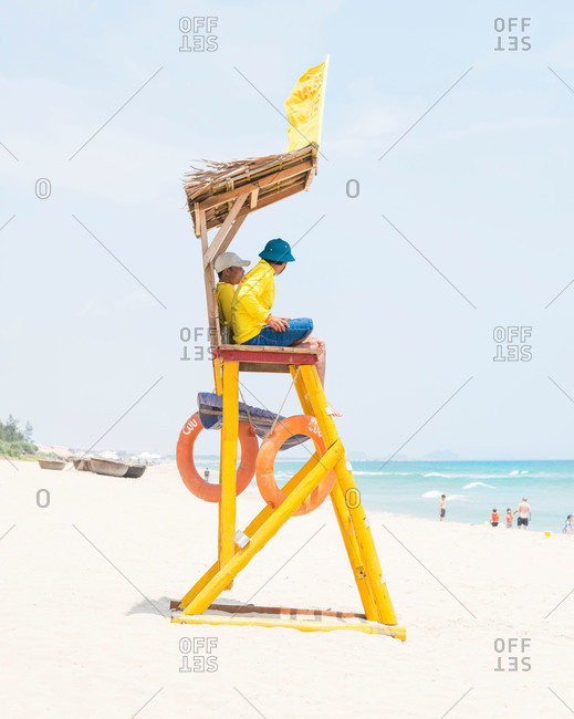 Bang Beach, Hoi An, Vietnam - April 27, 2015: Two lifeguards sitting in their tower on An Bang Beach, Hoi An, Vietnam