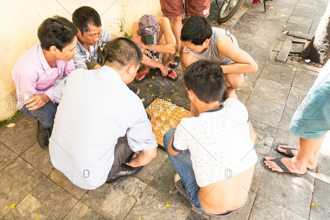 Hanoi, Vietnam - May 18, 2015: A group of men playing a board game on the pavement in Hanoi, Vietnam