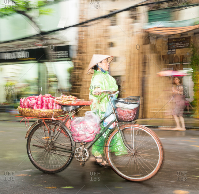Hanoi, Vietnam - May 15, 2015: A street vendor with her bicycle basket full of sweet potatoes pushes it down the street in the rain, Hanoi, Vietnam