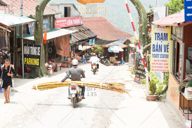 Cat Cat Village, Sapa, Vietnam - May 10, 2015: A man carrying bamboo on the back of his motorbike enters Cat Cat Village in the Sapa region of Vietnam