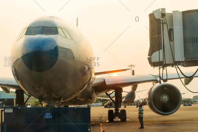 Saigon, Vietnam - April 10, 2015:  A jet airliner on the tarmac at sunset in Saigon, Vietnam