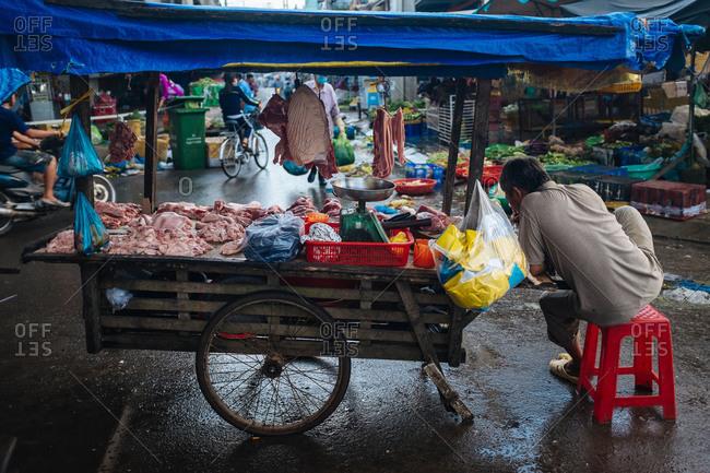 Phu Quoc, Vietnam - November 10, 2015: A man eats breakfast at a butcher's stall on Phu Quoc Island, Vietnam