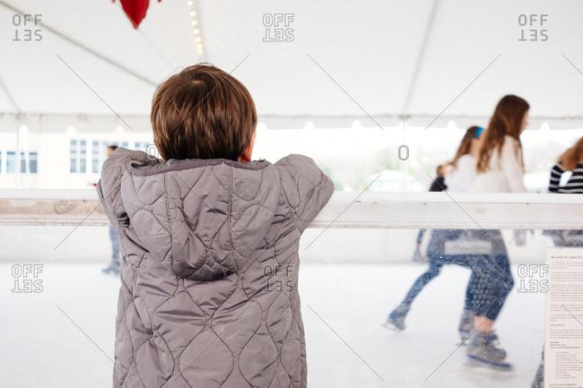 Boy watching kids ice skating