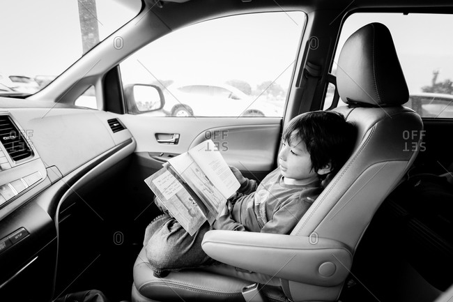 Boy reading a book riding in car front seat