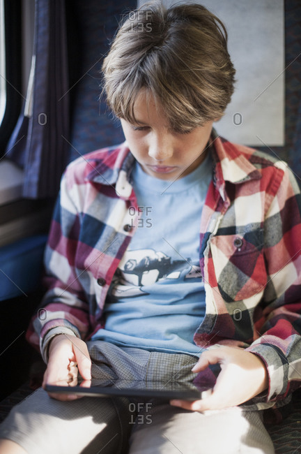 Boy sitting in a vehicle playing on an electronic tablet