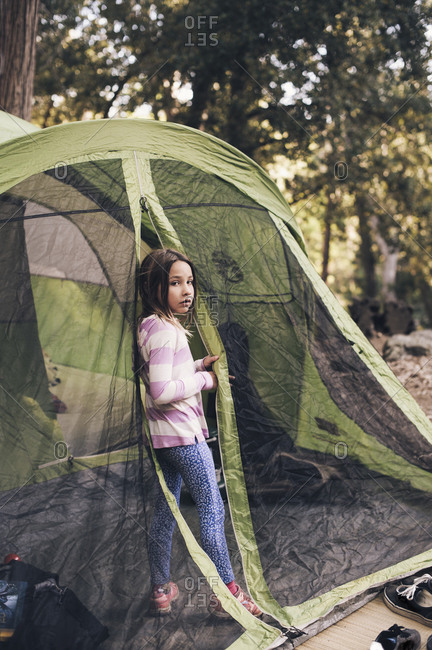 Little girl standing at the entrance of a camping tent