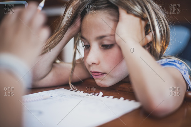 Girl watching her brother do homework