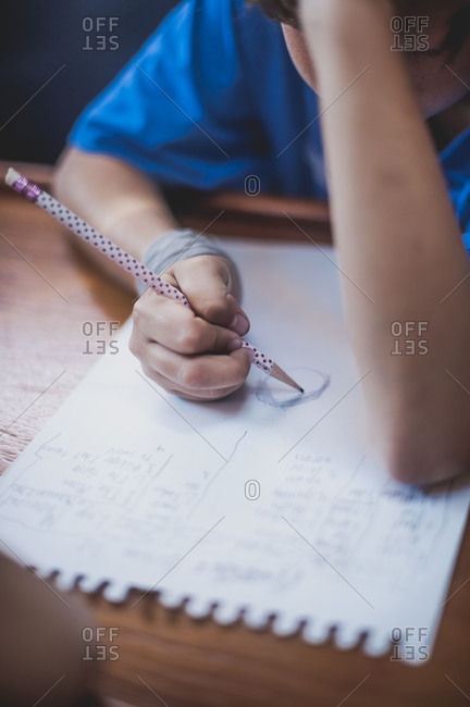 Boy doing homework at a wooden table