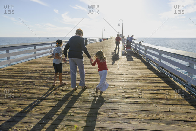 Grandmother walking with her grandkids on a pier