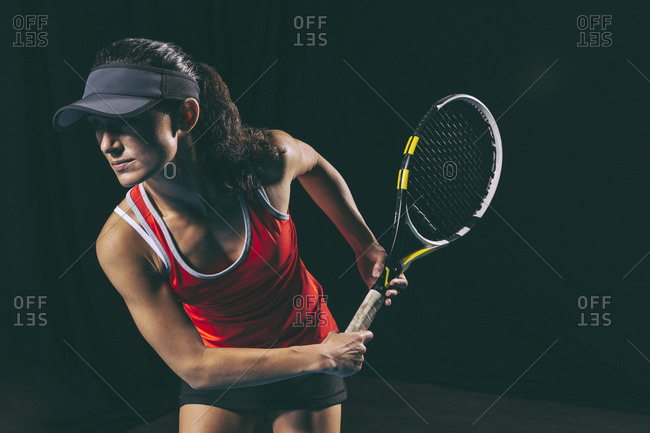 Brunette athletic woman with a tennis racquet