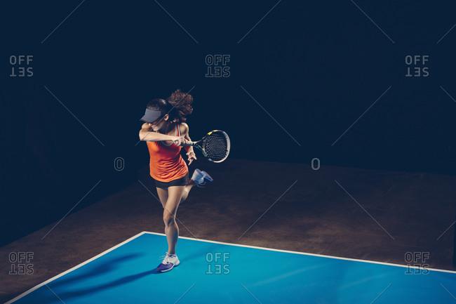 Brunette athletic woman on a blue tennis court