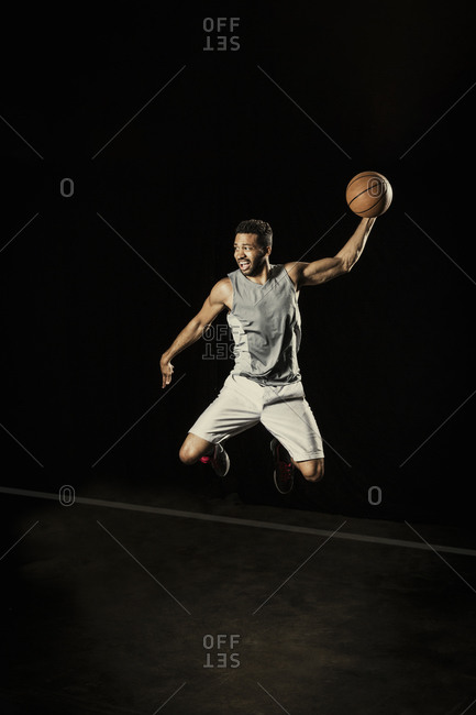 Athletic man jumping in the air with a basketball