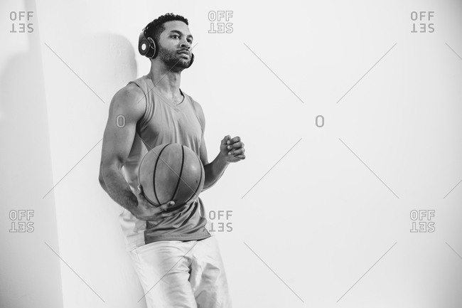 Athletic man holding a basketball and listening to music