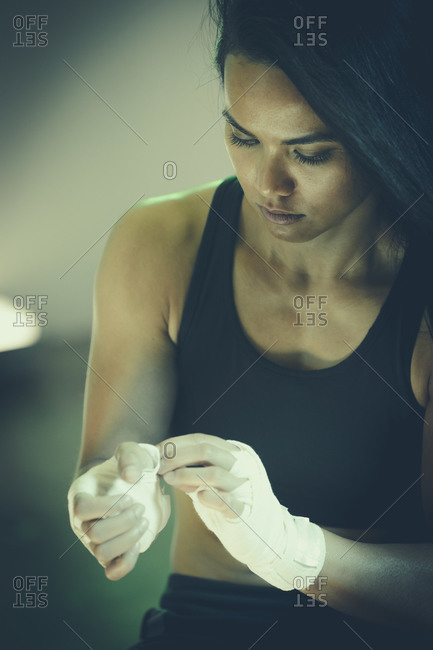Female boxer wrapping her hands
