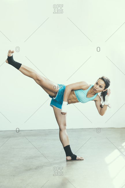 Portrait of a female kick-boxer with her leg in the air