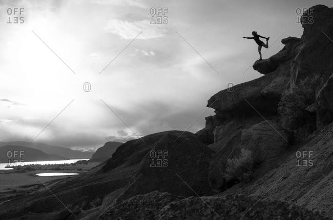 Woman in a yoga pose on a rocky hill