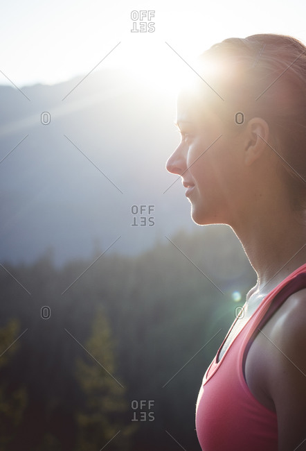 Portrait of a woman runner overlooking a wooded valley