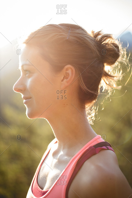 Portrait of a female runner looking at a wooded valley