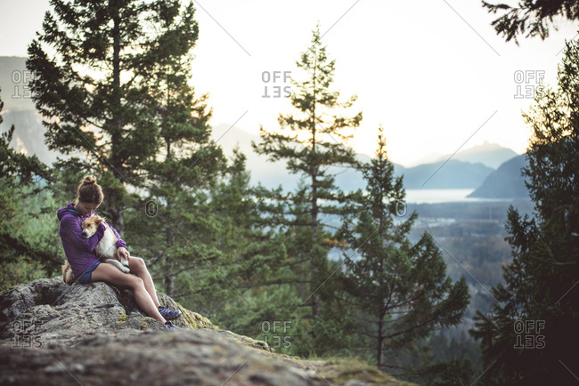 Runner holding her dog on a mountain overlooking a valley