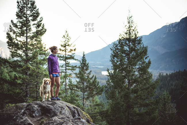 Runner standing on a rock with her dog overlooking a valley