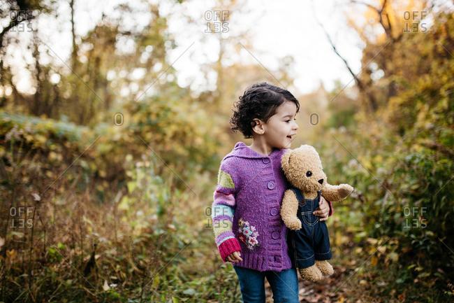 Little girl walking outside with her teddy bear